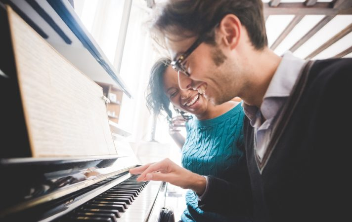 Young handsome mixed race couple in their house both playing piano. Focus on the woman looking at his man laughing - relaxing, love, relation concept